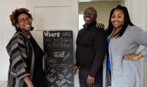 Three smiling Black people stand around a chalkboard sign.