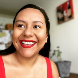 square portrait of Brenda Rodriguez Lopez, a brown woman with long black hair smiling to the left of the camera. She is wearing red lipstick and a red top.
