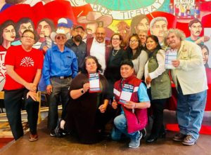 Image of PCUN organizers standing together in a group in front of a bright mural depicting Latine farm workers. They are holding pamphlets and looking into the camera.