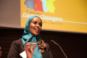 Picture of Ubax Gardheere. A Black woman wearing a turquoise headscarf and speaking animatedly into a microphone with a yellow background.
