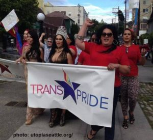 Image of UTOPI members marching at a pride parade holding a UTOPIA banner with their fists raised.