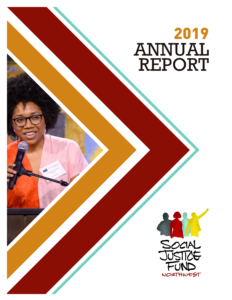 Front cover of the 2019 annual report. Rectangular image with white background. Layered chevron shapes in orange, crimson, and light blue point from the left side of the image to the right. Inside the chevrons is a picture of Carolanne Sanders SJF board member a Black woman wearing a pink and orange dress with a fro smiling and speaking into a microphone. Black text reads 2019 annual report. The SJF logo is in the bottom right corner.