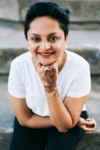 Picture of Ankita Patel a South Asian woman with short black hair and red lipstick wearing a white t shirt. She has a henna design on her left hand. She leans her head on her fist and smiles at the camera.