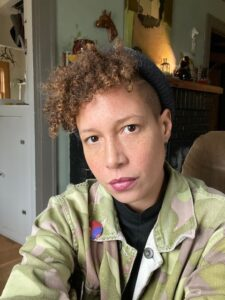 Picture of Aviva McClure a Giving Project member. They are a Black person with light skin and warm brown curly hair wearing a black hat black shirt and an camo print jacket. They look seriously into the camera.
