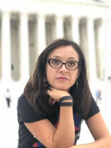 Picture of Palmira Figueroa. A white Latinx woman wearing a black t shirt and black glasses gazing up and away from the camera with a curious look on her face.