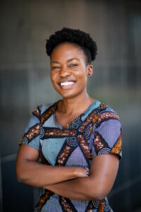 Picture of Akoth. A smiling Black person with their hair up in a puff wearing a blue and purple printed shirt and crossing their arms.