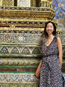 Picture of Alice Wu cohort member. Alice is an Asian person with long black hair dyed blonde at the tips. She is wearing a printed jumpsuit and standing in front of an elaborately painted wall.